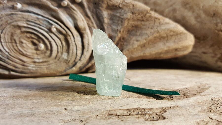 """Neapstrādāts akvamarīna kristāls """"Emociju līdzsvaram"""" nr 3. Izmērs 2.6 x 1.5 cm Zaļa bantīte"""
