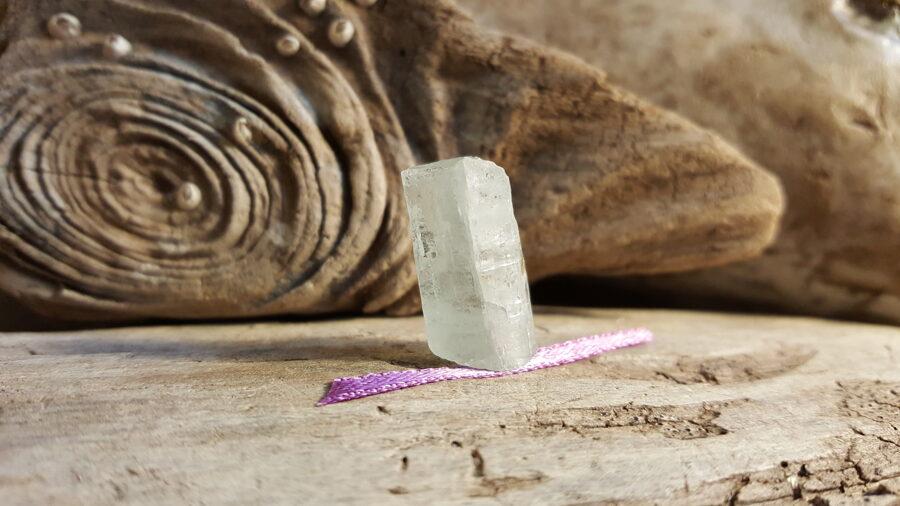 """Neapstrādāts akvamarīna kristāls """"Emociju līdzsvaram"""" nr 6. Izmērs 2.5 x 1.4 cm Lillā bantīte"""