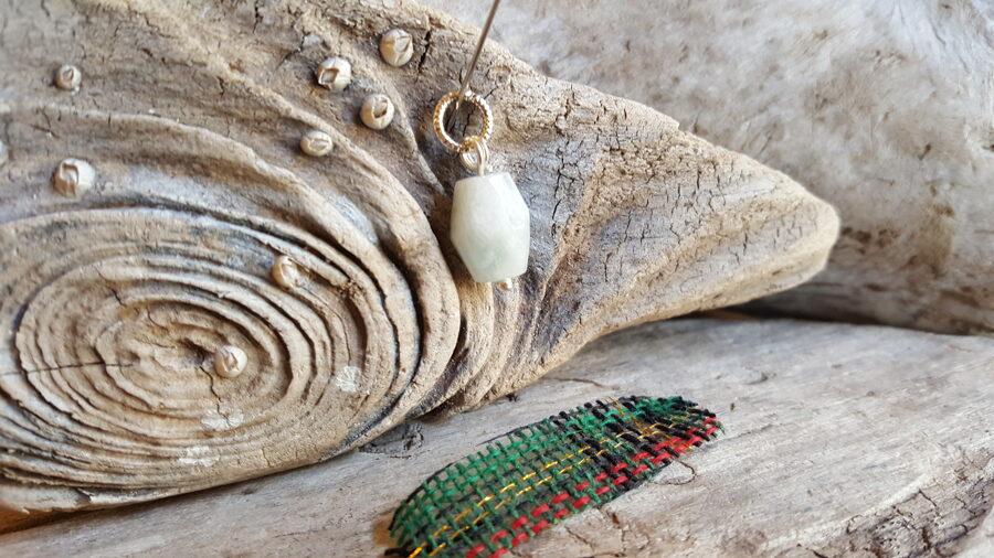 Akvamarīna kulons nr 4. Izmērs 1.5 x 1 cm Sudaraba krāsas detaļas Zaļi rūtaina bantīte