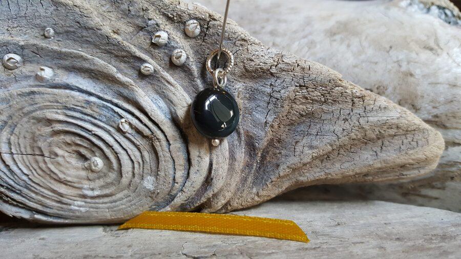 """Obsidiāna kulons """"Plakanais"""" nr 5. Izmērs 1.2 cm Dzeltena bantīte Sudraba krāsas metāls"""