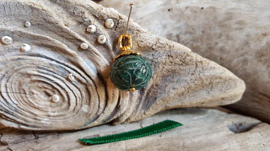 """Smaragda kulons """"Atbalsts ikdienā"""" nr 3. Izmērs 1.8 x 1.7 cm Zaļa bantīte Gravējums Zelta krāsas detaļas"""