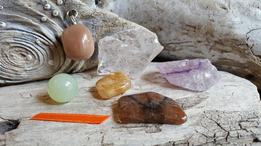 """Komplekts """"Emociju līdzsvaram"""" nr 1. Oranža bantīte Kalnu kristāls (neapstrādāts) Ametists (neapstrādāts) Hiastolīts Saules akmens Serpentīns (lode) Citrīns"""