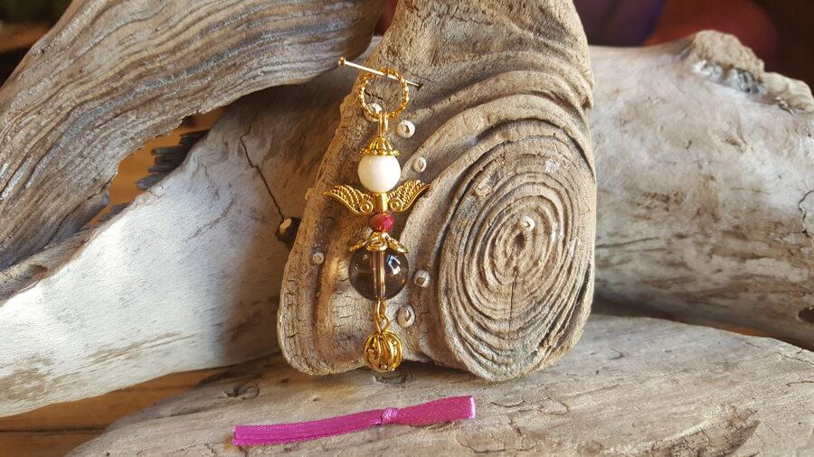 Dūmkvarca eņģelis nr 1. Izmērs 5 x 1.2 cm Zelta krāsas metāls Rozā bantīte