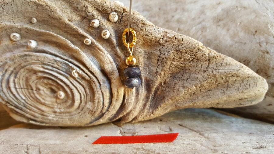 """Safīra kulons """"Pārticība"""" nr 4. Izmērs 1.4 x 0.7 cm Sarkana bantīte Zelta krāsas metāls"""