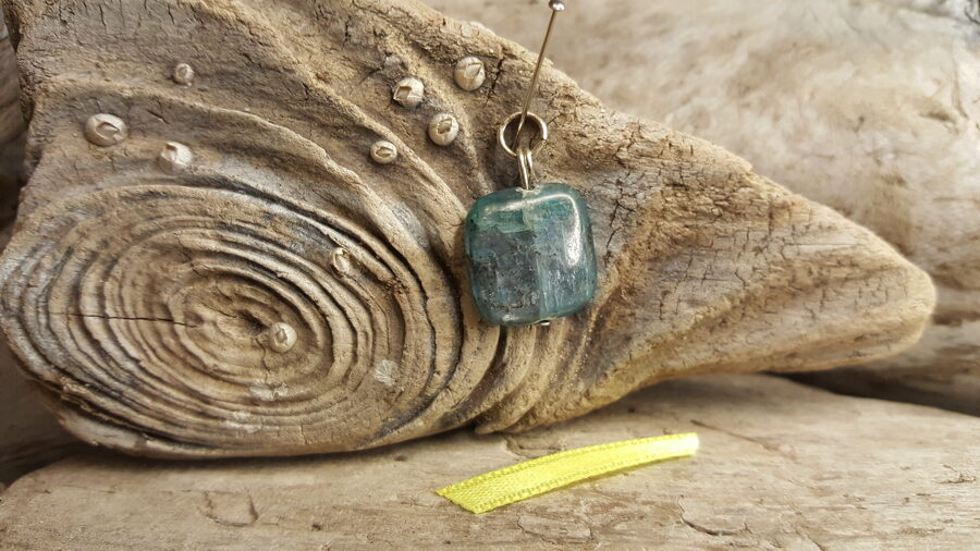 """Kianīta kulons """"Piedot"""" nr 1. Izmērs 1.2 x 1.5 cm Dzeltena bantīte Sudraba krāsas metāls Ar dabīgiem iekļāvumiem"""