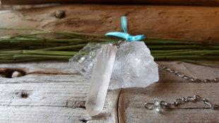 Kalnu kristāla svārstiņš no dabīga kristāla ar zilu lentīti. Kristāla izmērs ir 4cm.