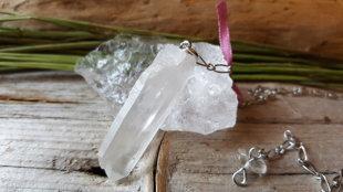 Kalnu kristāla svārstiņš no dabīga kristāla ar rozā bantīti. Kristāla izmērs ir 4 cm